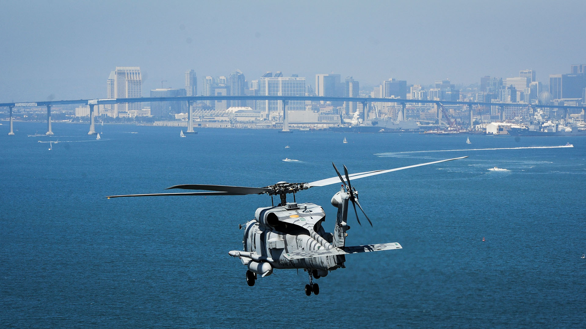 US Navy MH-60R Seahawk helicopter flies over San Diego City during daytime