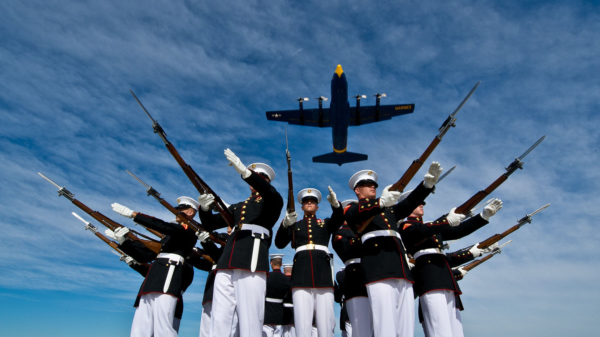 Marines stand at attention and salute with rifles while blue angels c-130 flies overhead during daytime